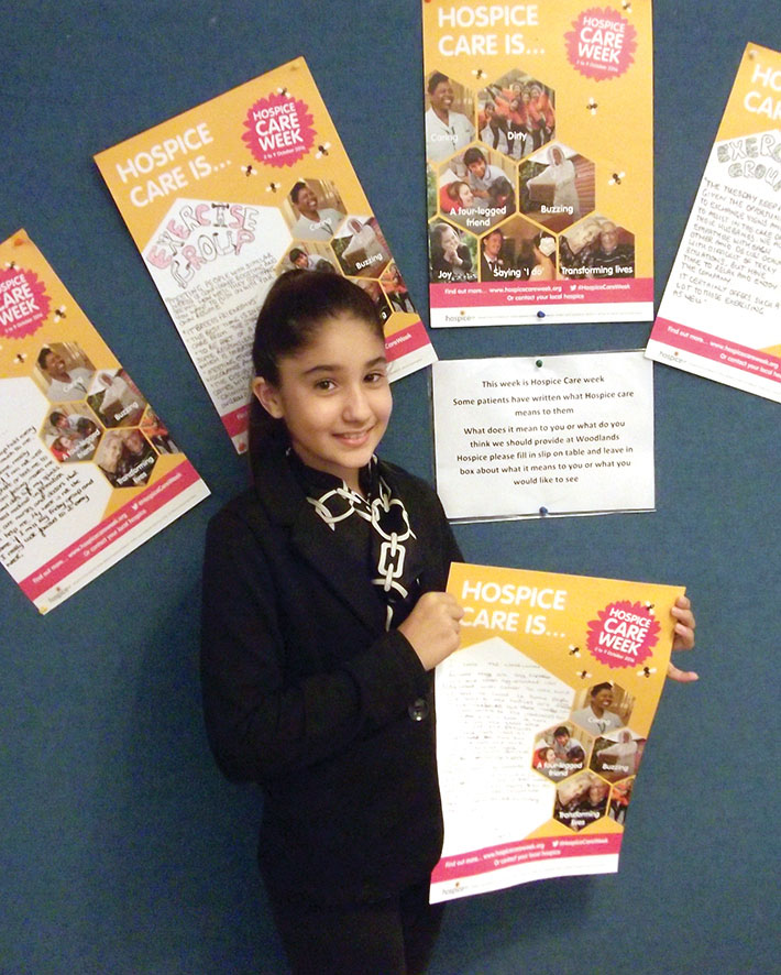 Indira holding her Hospice Care week poster. On the poster she wrote about the Hospice and what it means to her.