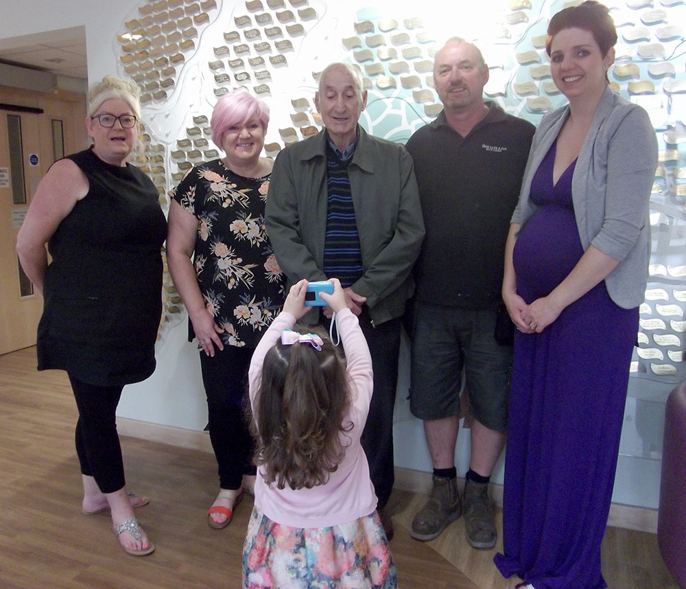 The family of Margaret Carr visit Woodlands Hospice Tree of Life to place their leaf on it